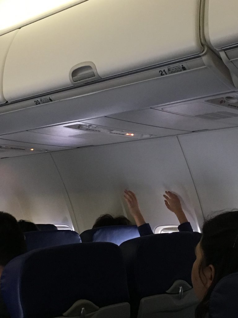 Little boy on airplane with hands up in the air during turbulence